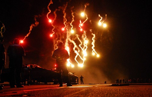 080704-N-0640K-271 PACIFIC OCEAN (July 4, 2008) Sailors watch flares light up the sky during a Navy-style fireworks display on the flight deck of the Nimitz-class aircraft carrier USS Ronald Reagan (CVN 76). The ship held a surface power demonstration for the crew in honor of the Fourth of July holiday. Other festivities for Independence Day included a steel beach picnic and a root beer float social. The Ronald Reagan Carrier Strike Group is on a scheduled deployment in the U.S. 7th Fleet area of responsibility. U.S. Navy photo by Mass Communication Specialist 2nd Class Jennifer S. Kimball (Released)