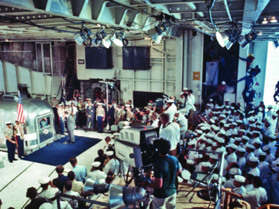 Sailors watch behind the press as Nixon addresses the Apollo 11 astronauts.