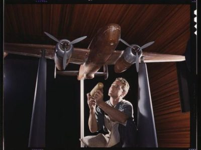 An experimental scale model of the B-25 plane is prepared for wind tunnel tests in the plant of the North American Aviation, Inc., Inglewood, Calif. The model maker holds an exact miniature reproduction of the type of bomb the plane will carry.