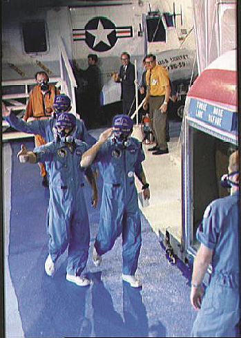 The Apollo 12 astronauts walk into their Mobile Quarantine Facility aboard Hornet.