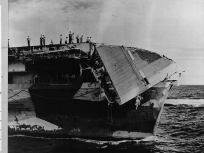 The collapse of Hornet's flight deck bow section due to typhoon wind and water damage.