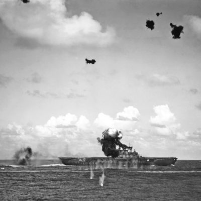 A Japanese Aichi D3A1 Val Dive Bomber crashes into the signal bridge of Hornet during the first attack of the Battle of Santa Cruz Islands. Photograph taken from USS Pensacola (CA-24).