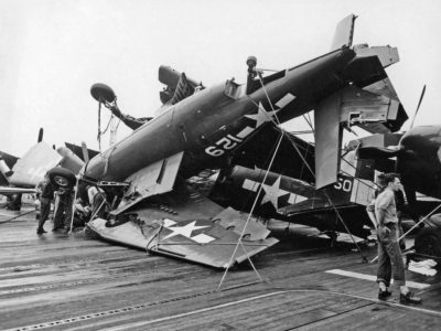 Damage to planes on flight deck of Hornet by typhoon winds and water. An over turned TBM-3C Avenger in foreground.