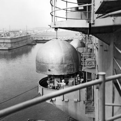 A crane lifting DH dome from a gun tub aboard the USS Hornet (CV-12) during reactivation.