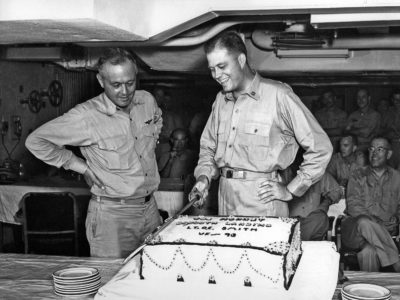 CAPT. Frank A. Brandly, USN, C. O. of Hornet looks on admiringly as LT. Carl E. Smith, USN, VF-93 cuts cake baked to celebrate his landing on 1 October 1954 making the 30,000th landing on Hornets (CV-12) and (CVA-12).